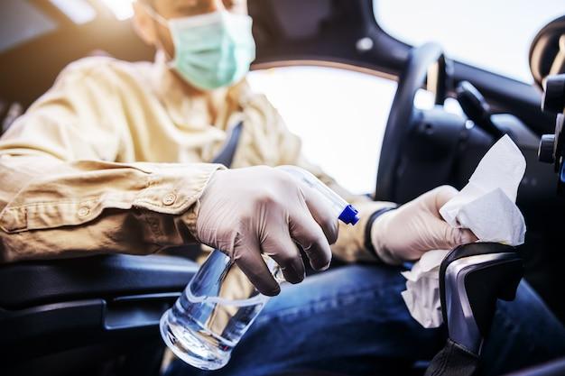 남성복을 입은 남자는 차 안에서 마스크를 소독하고, 자주 만지는 깨끗한 표면을 닦고, covid-19 바이러스 감염, 세균 또는 박테리아 오염을 방지합니다. 감염