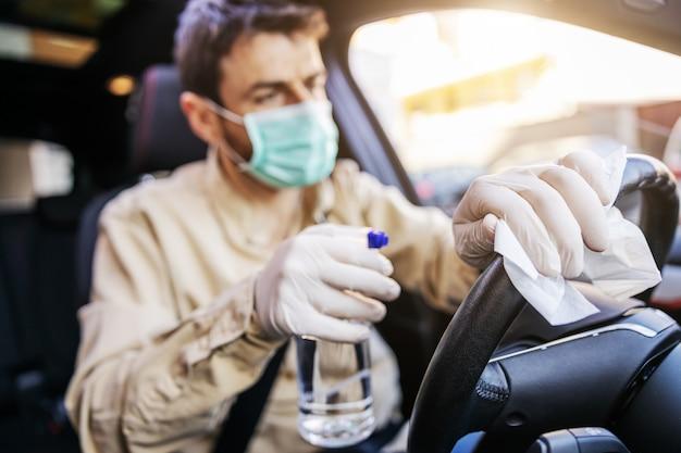 남성복을 입은 남자는 차 안에서 마스크를 소독하고, 자주 만지는 깨끗한 표면을 닦고, covid-19 바이러스 감염, 세균 또는 박테리아 오염을 방지합니다.