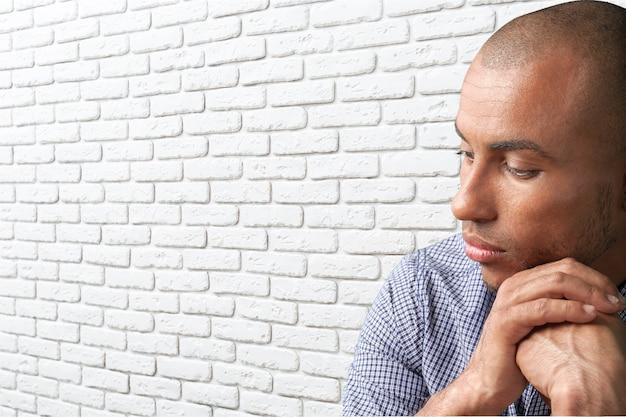 Человек в эмоциональном стрессе, держа голову руками, изолированными на белом