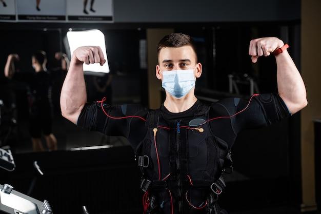 Человек в костюме ems и медицинской маске в тренажерном зале
