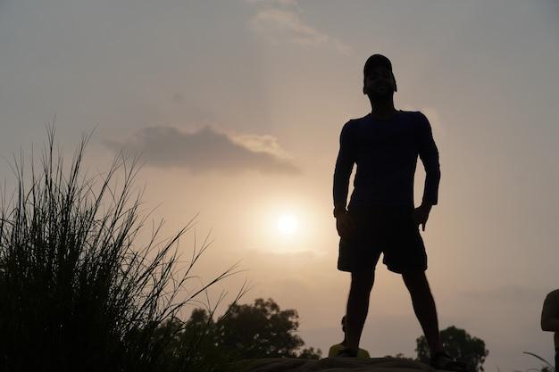 서 있는 태양 근처 저녁에 남자