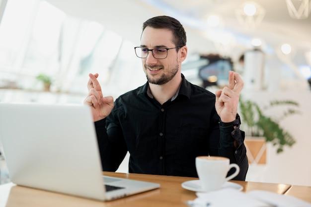 眼鏡と黒いシャツを身振りで示す指を交差させて笑っている男。運と迷信の概念。彼のラップトップでカメラで話す、カフェに座っているひげを持つ若い魅力的な男。