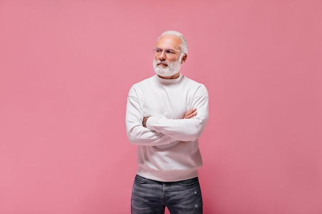 Человек в очках и свитере позирует на изолированной стене