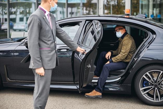Человек в очках выходит из элитного такси