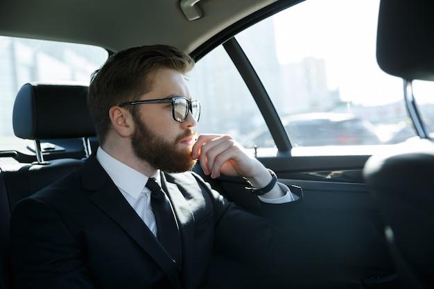 車の後部座席に座っている眼鏡の男