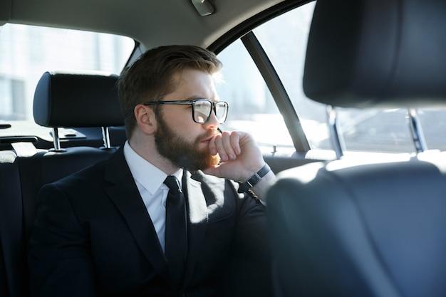 Человек в очках сидит на заднем сиденье автомобиля