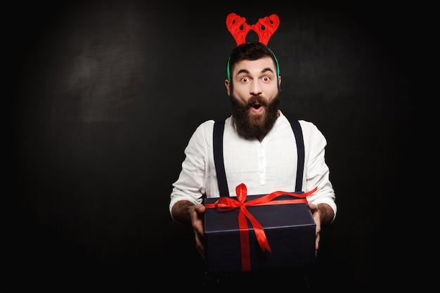 Человек в поддельных оленьих рогов, держа рождественский подарок на черном фоне.