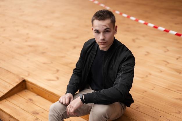 Человек в модной одежде сидит на деревянном полу на открытом воздухе