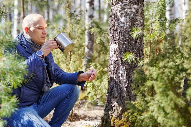 Человек в лесу пьет из сока дерева чашки