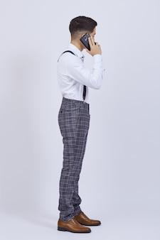 Человек в официальном платье, стоя разговаривает по телефону на белом