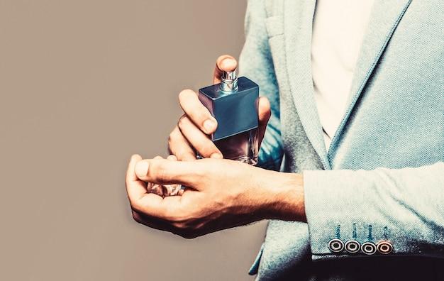 フォーマルなスーツを着た男、香水のボトル、クローズアップ。香りのにおい。男性の香水。ファッションケルンボトル。香水のボトルを持っている男。スーツの背景に手に男性の香水。スペースをコピーします。
