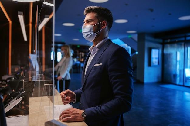 高級ホテルのレセプションに立ってチェックインするフェイスマスクを持ったフォーマルウェアの男性。