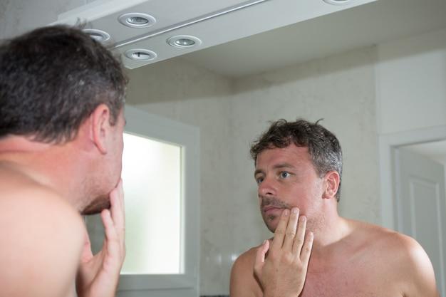 Человек перед зеркалом смотрит на подбородок