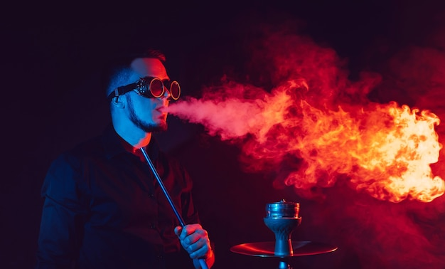 미래의 안경을 쓴 남자는 물 담뱃대를 피우고 빨간색과 파란색 네온 불빛이있는 물 담배 바에서 연기 구름을 불어 넣습니다.