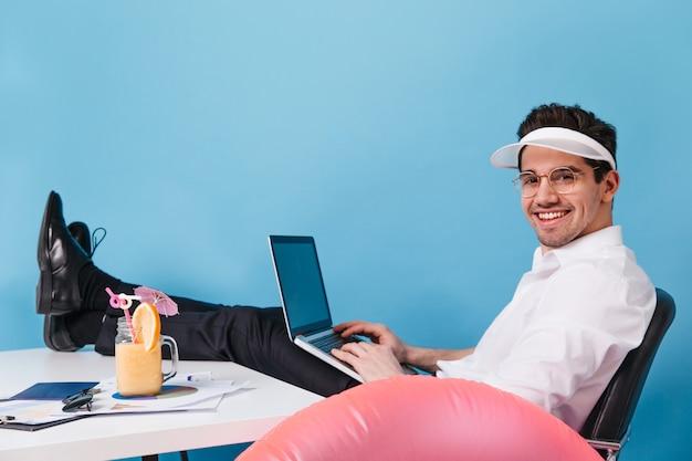 Человек в очках и кепке работает на изолированном пространстве. парень позирует с ноутбуком, коктейлем и надувным кругом.