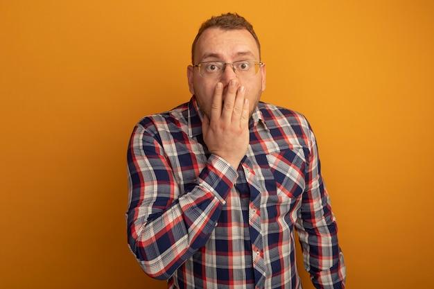 안경에 남자와 체크 셔츠는 오렌지 벽 위에 서있는 손으로 입을 덮고 충격을 받고