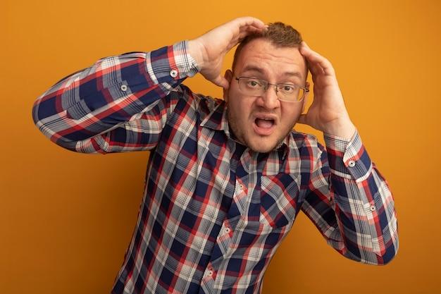 オレンジ色の壁の上に立っている彼の頭の上の手で失望している眼鏡とチェックシャツの男