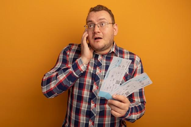 안경과 체크 셔츠를 입은 남자가 옆으로 놀란 표정으로 항공 티켓을 들고 오렌지 벽 위에 서서 놀랐습니다.