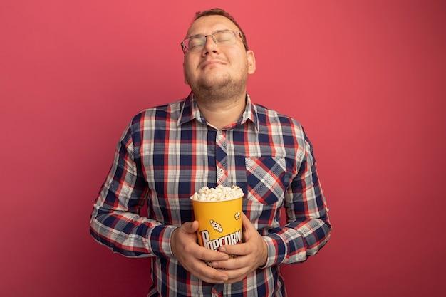 Мужчина в очках и клетчатой рубашке держит ведро с попкорном, глядя с закрытыми глазами, чувствуя положительные эмоции, стоя над розовой стеной