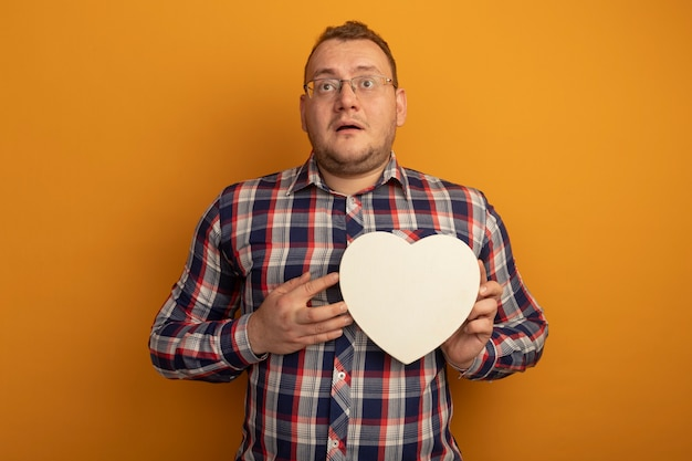 オレンジ色の壁の上に立って困惑して脇を見ているcardboradハートを保持している眼鏡とチェックシャツの男