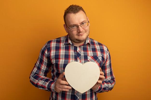 オレンジ色の壁の上に立って自信を持って笑顔のcardboradハートを保持している眼鏡とチェックシャツの男