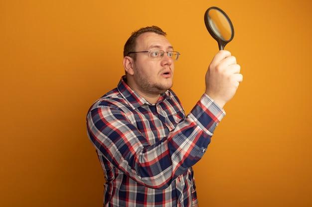 돋보기를 들고 안경과 체크 셔츠를 입은 남자는 주황색 벽 위에 서서 흥미를 느낍니다.
