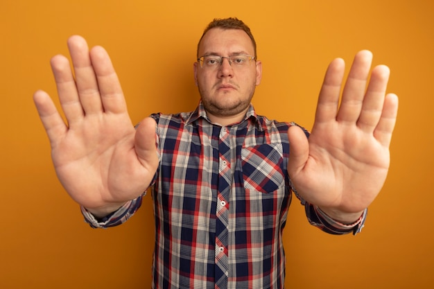 Мужчина в очках и клетчатой рубашке делает стоп-жест с открытыми руками с серьезным лицом, стоящим над оранжевой стеной