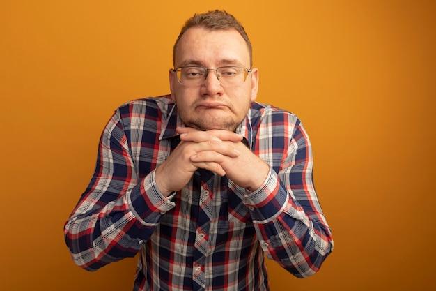 오렌지 벽 위에 서있는 안경과 체크 셔츠에 피곤하고 지루한 남자