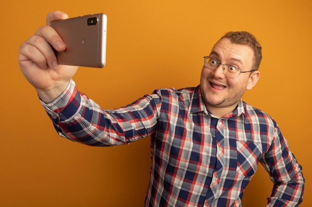 オレンジ色の壁の上に元気に立って笑顔で自分撮りをしているスマートフォンを使用して眼鏡とチェックシャツの男