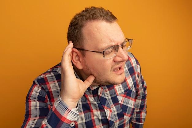 오렌지 벽 위에 서있는 수군을 듣고 귀 위로 손으로 안경과 체크 셔츠를 입은 남자