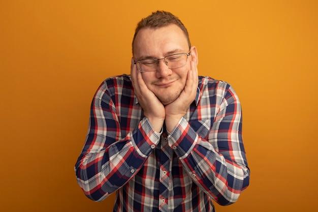 Человек в очках и клетчатой рубашке с руками возле лица счастливым и веселым, чувствуя положительные эмоции, стоя над оранжевой стеной