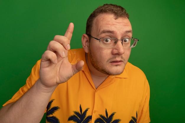 緑の壁の上に立っている新しいアイデアを持って指を上げて驚いた眼鏡とオレンジ色のシャツの男