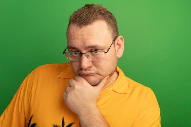 녹색 벽 위에 서있는 얼굴 생각에 잠겨있는 표정으로 안경과 오렌지 셔츠에 남자