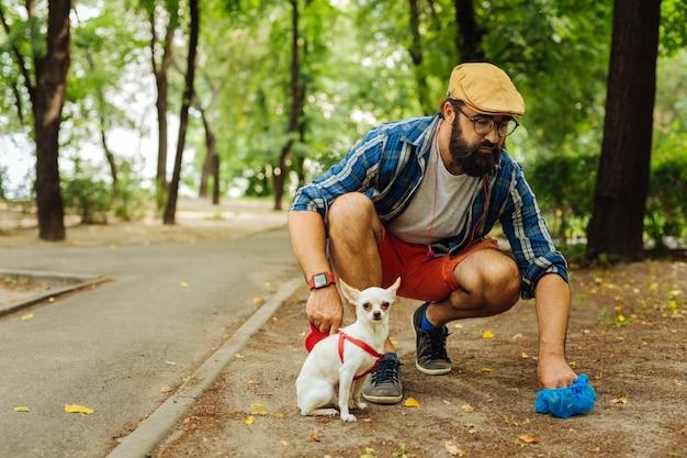 안경 남자. 공원에서 산책하는 그의 개를 돌보는 검은 안경을 쓰고 수염이 세련된 남자