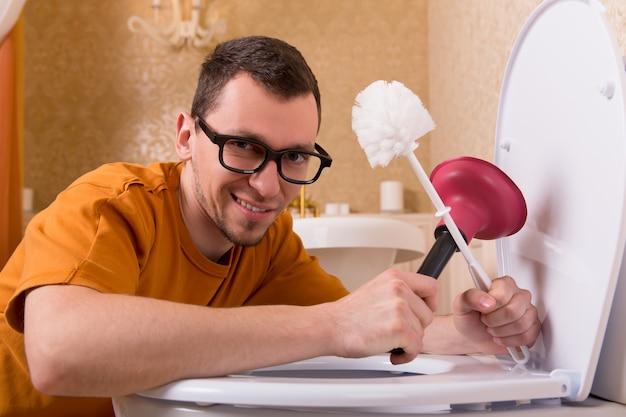 Человек в очках чистит унитаз
