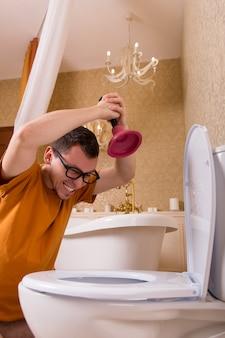 Мужчина в очках убирает засор в унитазе. роскошный интерьер ванной комнаты