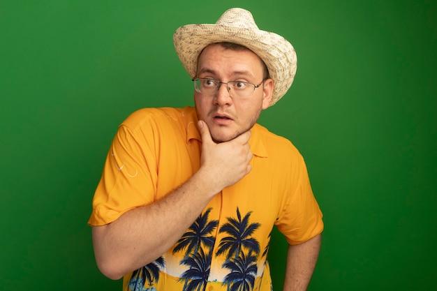주황색 셔츠와 여름 모자를 쓰고 안경을 쓴 남자는 녹색 벽 위에 서서 당황해합니다.