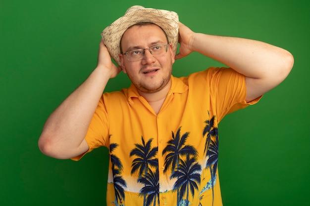 녹색 벽 위에 서있는 그의 머리 뒤에 hnads와 함께 행복 한 얼굴로 옆으로 찾고 오렌지 셔츠와 여름 모자를 쓰고 안경에 남자