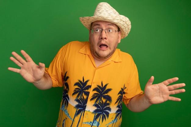 주황색 셔츠와 여름 모자를 쓰고 안경을 쓴 남자는 녹색 벽 위에 서있는 팔로 걱정하고 무서워합니다.