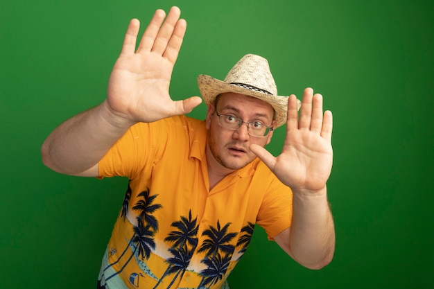 오렌지 셔츠와 여름 모자를 쓰고 손으로 방어 제스처를 만드는 안경에 남자가 녹색 벽 위에 서 무서워하는