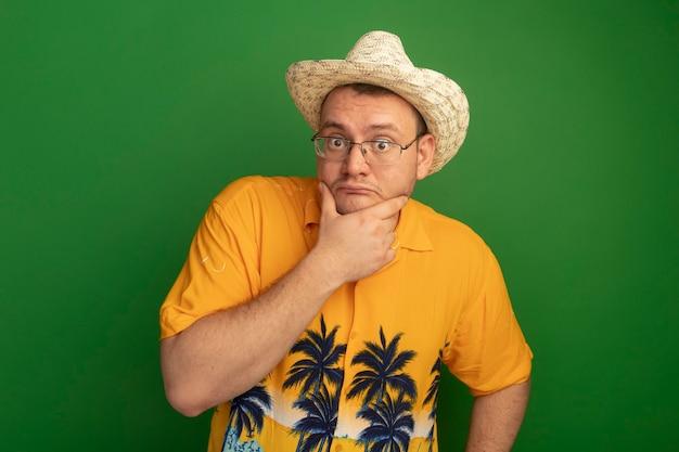 주황색 셔츠와 여름 모자를 쓰고 안경을 쓴 남자는 녹색 벽 위에 서 의아해했다.