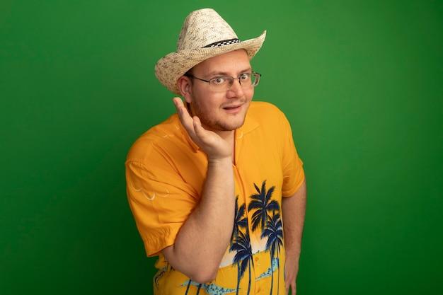 녹색 벽 위에 서 웃는 얼굴 근처 손으로 오렌지 셔츠와 여름 모자를 쓰고 안경에 남자