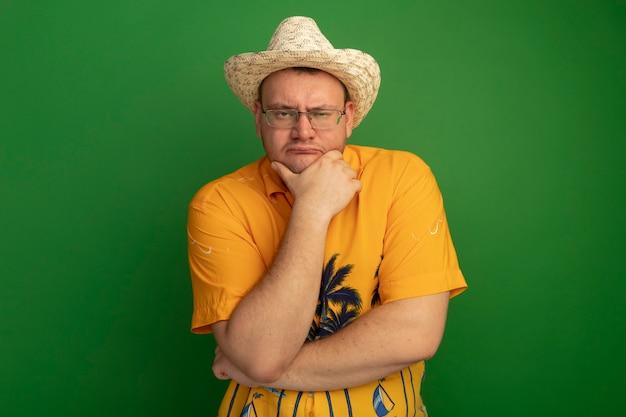 녹색 벽 위에 서있는 얼굴 생각에 잠겨있는 표정으로 오렌지 셔츠와 여름 모자를 쓰고 안경 남자