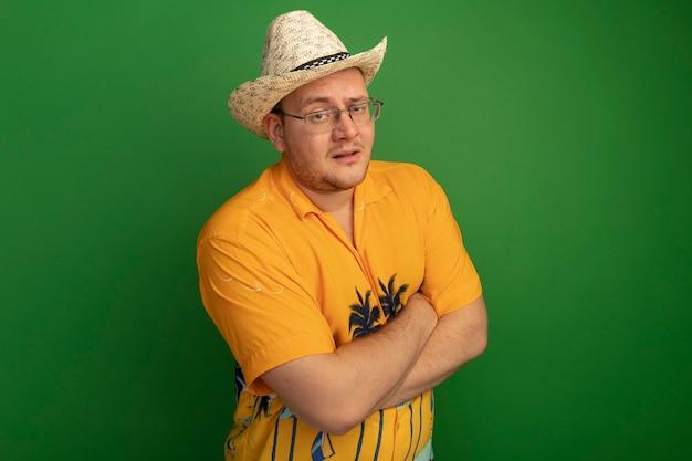 녹색 벽 위에 서있는 팔을 교차 심각한 얼굴로 오렌지 셔츠와 여름 모자를 쓰고 안경 남자