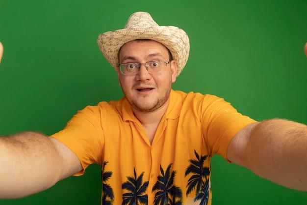 녹색 벽 위에 서있는 얼굴에 미소로 오렌지 셔츠와 여름 모자를 쓰고 안경에 남자