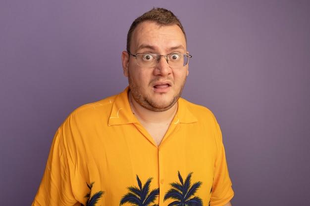 주황색 셔츠를 입고 안경에 남자가 혼란스럽고 보라색 벽 위에 서서 걱정