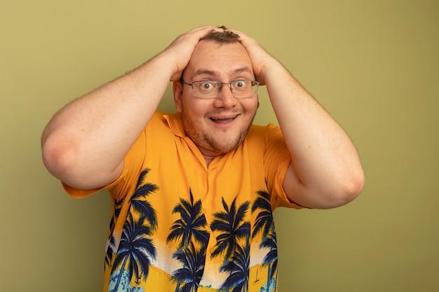 緑の壁の上に立っている彼の頭の上の手で幸せで興奮しているオレンジ色のシャツを着た眼鏡の男