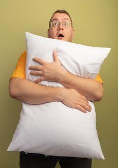 明るい壁の上に立って驚いて驚いて見上げる枕を抱き締めるオレンジ色のシャツを着た眼鏡の男