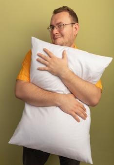 明るい壁の上にずる賢く立って笑っている枕を抱き締めるオレンジ色のシャツを着た眼鏡の男