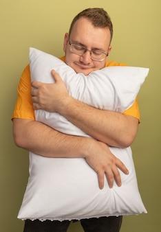 明るい壁の上に立っている前向きな感情を感じて目を閉じて枕を抱き締めるオレンジ色のシャツを着た眼鏡の男